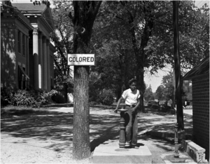 """An African-American youth at a segregated drinking fountain in Halifax, NC, 1938,"
