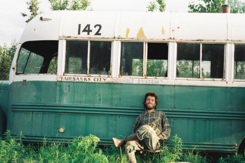 Christopher McCandless in front of the Alaskan bus where his body was found in 1992. Image via Confessions of a readaholic