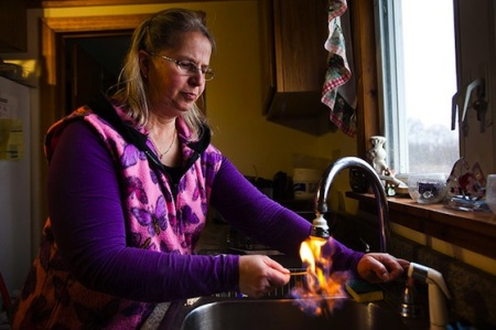 Sherry Vargson (Granville Summit, Pennsylvania), who has leased mineral rights under her farm to Chesapeake Energy, is seen lighting her well water on fire as it flows out of her kitchen tap. Image © Jim Lo Scalzo via GoMakeThings