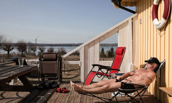 An inmate at Bastoy prison sunbathes. Image ©Marco Di Lauro via The Guardian