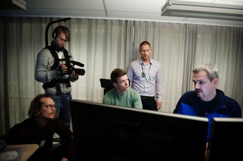 Håkon Høydal (left, sitting) and Einar Stangvik (middle, sitting) with members of the Norwegian police. Image © Therese Alice Sanne/VG.